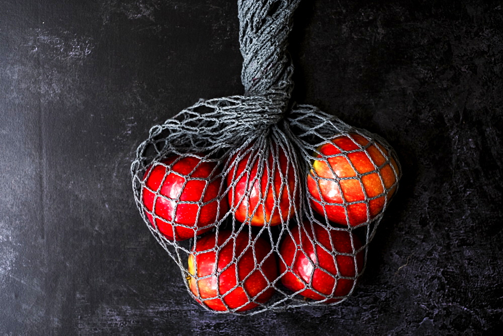 High angle close up of red apples in grey net bag on black background, United Kingdom