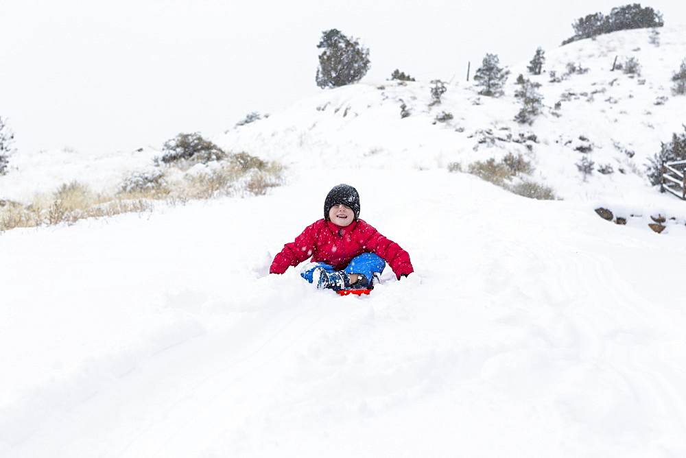 A boy and girl sledding down hill in snow, United States