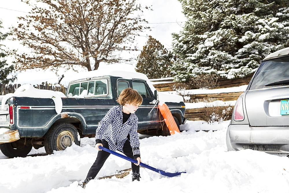 A young boy shoveling snow in driveway, United States