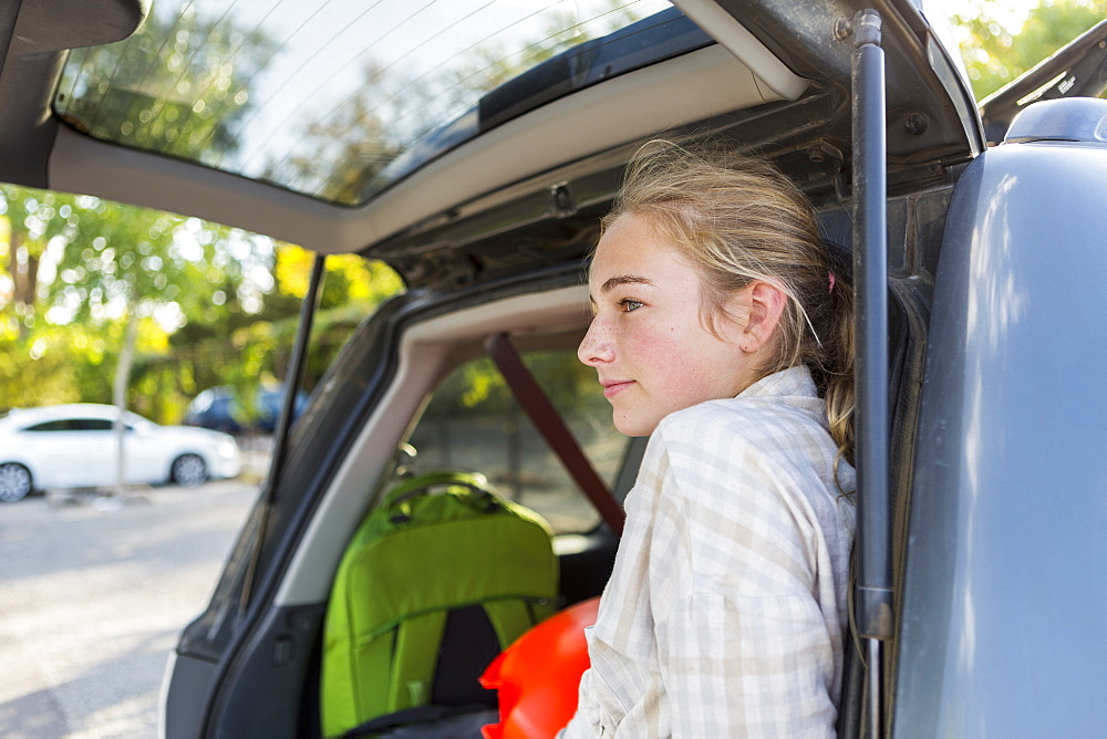 A teenage girl in the back of an SUV with luggage, United States