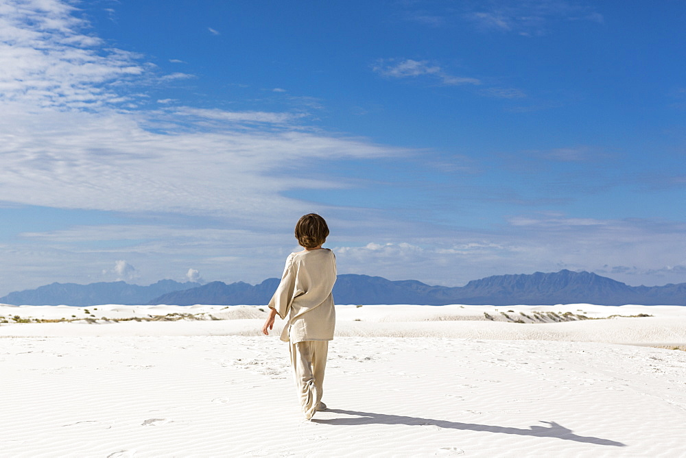 A young boy walking in sand dunes, White Sands National Monument, New Mexico, United States