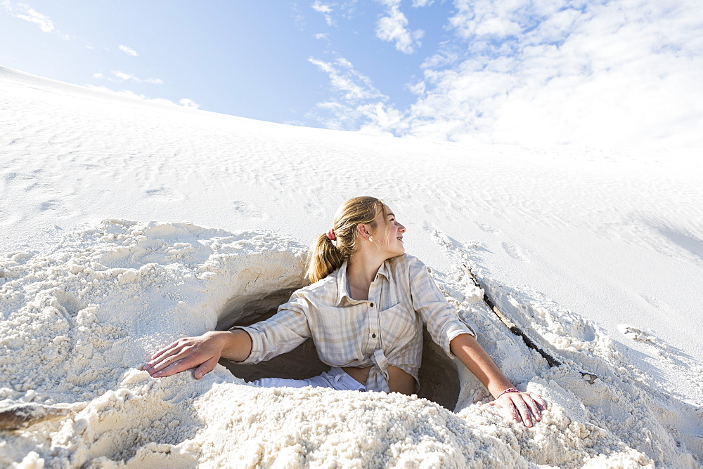 A teenage girl emerging from a dug out hole in white sand dunes, White Sands National Monument, New Mexico, United States - 1174-7925