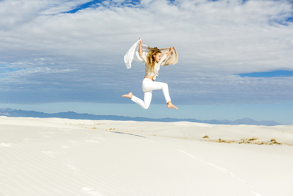 A teenage girl dancing and leaping n mid air in the open space on white sand dunes, White Sands National Monument, New Mexico, United States