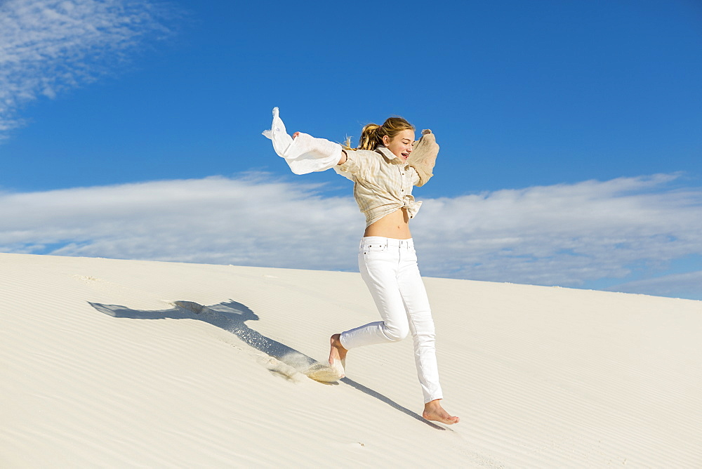 A teenage girl leaping and dancing in light white sand in a dunes landscape, White Sands National Monument, New Mexico, United States