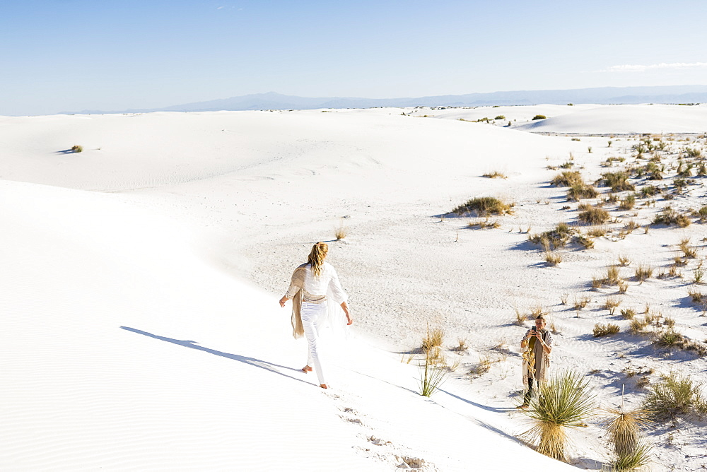 A teenage girl walking across sand dunes leaving footprints, White Sands National Monument, New Mexico, United States