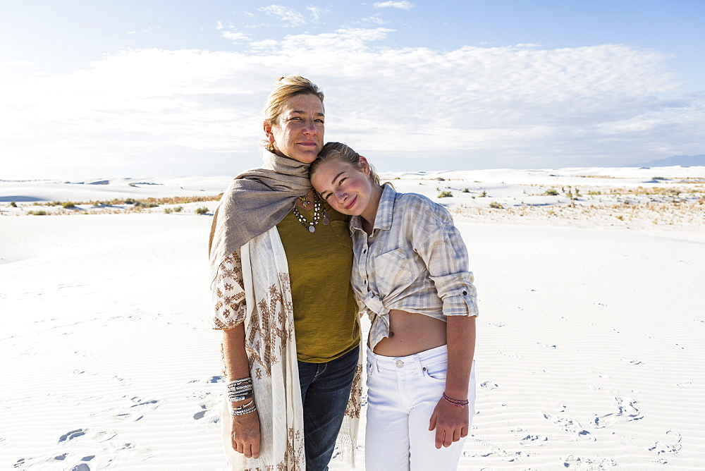 A mother and her teenage daughter side by side, arms around waists, in an open space, White Sands National Monument, New Mexico, United States