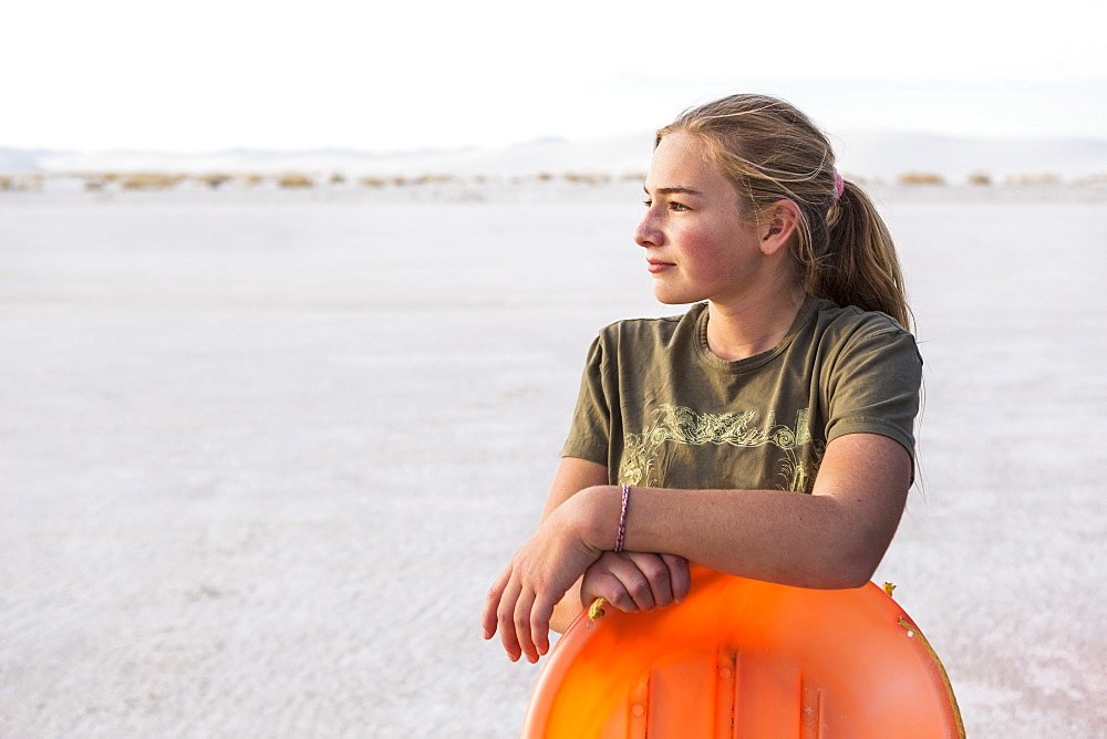 A teenage girl leaning on orange sled, White Sands National Monument, New Mexico, United States