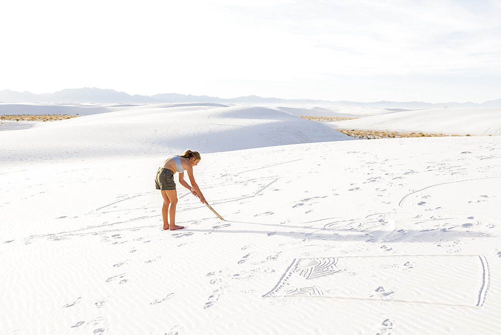 A teenage girl drawing in the sand, White Sands National Monument, New Mexico, United States