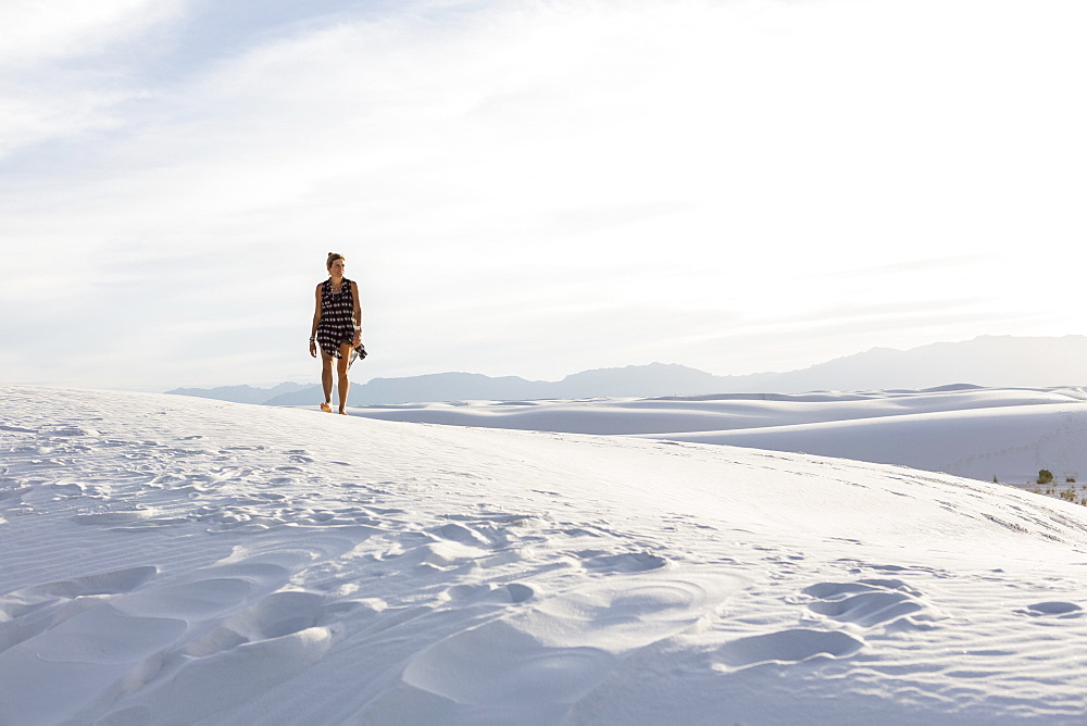 Woman walking in white sand dunes, White Sands National Monument, New Mexico, United States - 1174-7941