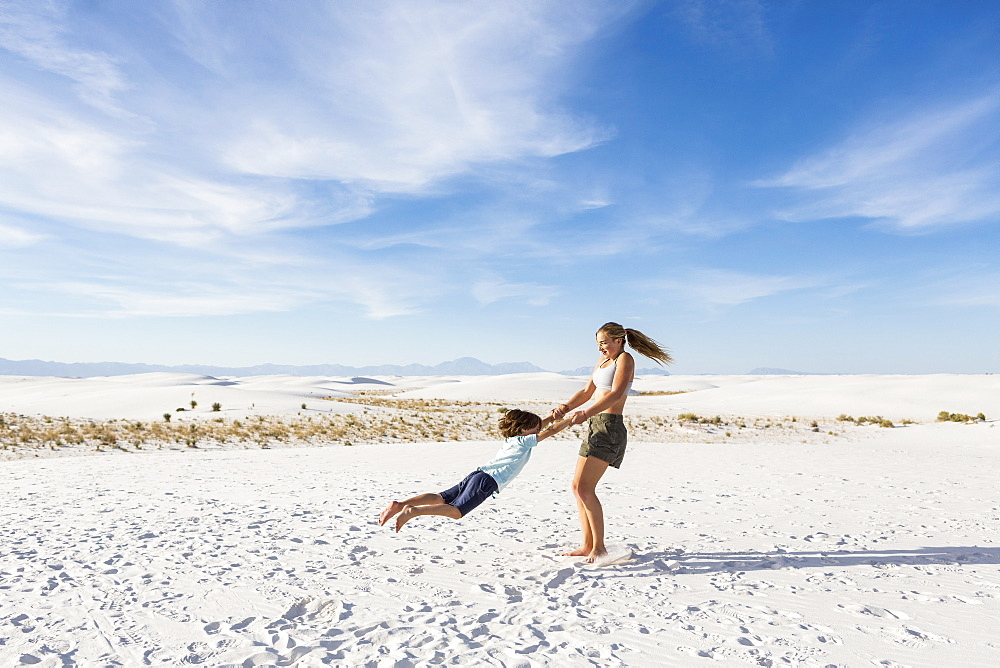 A teenage girl swinging her 6 year old brother in sand, White Sands National Monument, New Mexico, United States