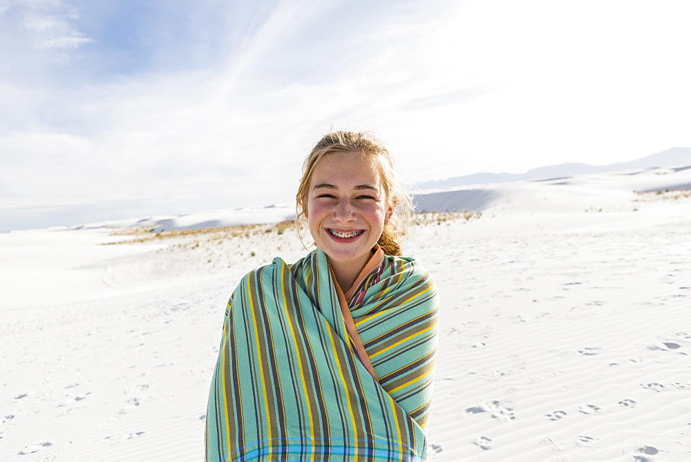 Teenage girl in a towel on the sand, White Sands National Monument, New Mexico, United States