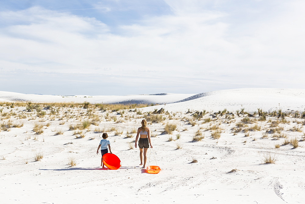 Two children pulling sledges, White Sands National Monument, New Mexico, United States