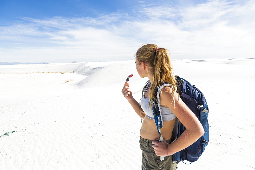 A teenage girl hiking across white sand dunes, White Sands National Monument, New Mexico, United States