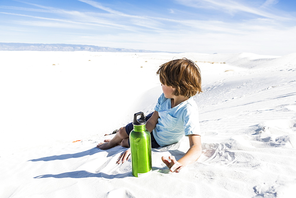 A young boy with green water bottle, White Sands National Monument, New Mexico, United States