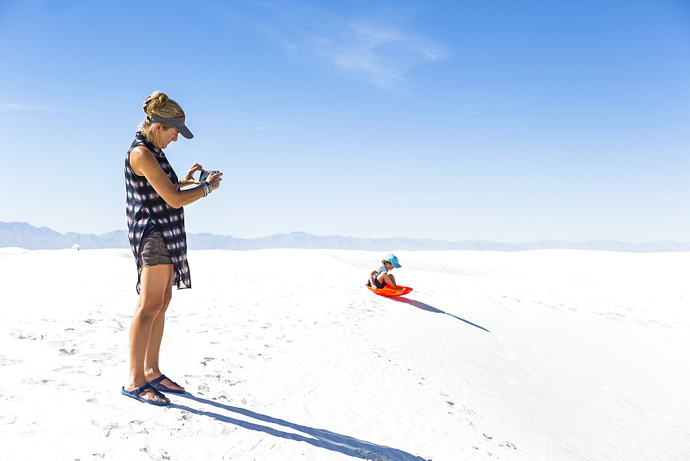 Mother taking picture of son sledding on sand dunes, White Sands National Monument, New Mexico, United States