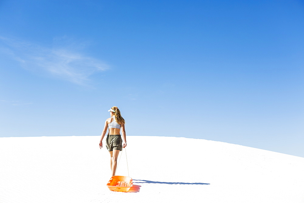 A teenage girl pulling a sled, White Sands National Monument, New Mexico, United States