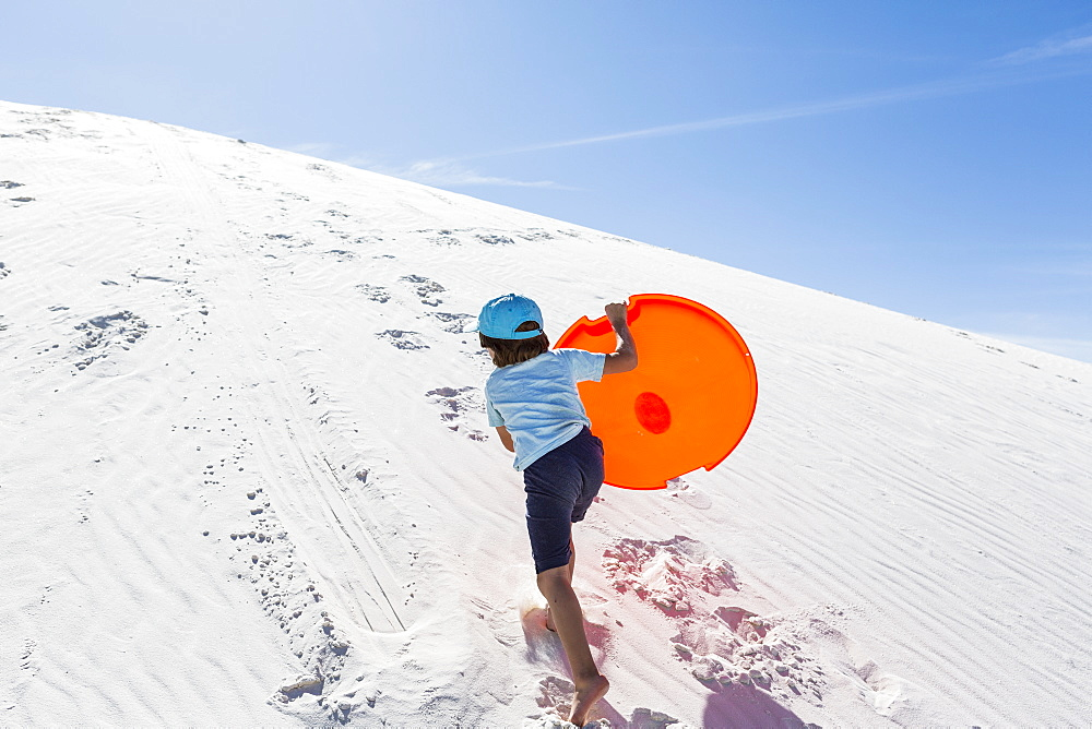 A young boy climbing sand dune, White Sands National Monument, New Mexico, United States