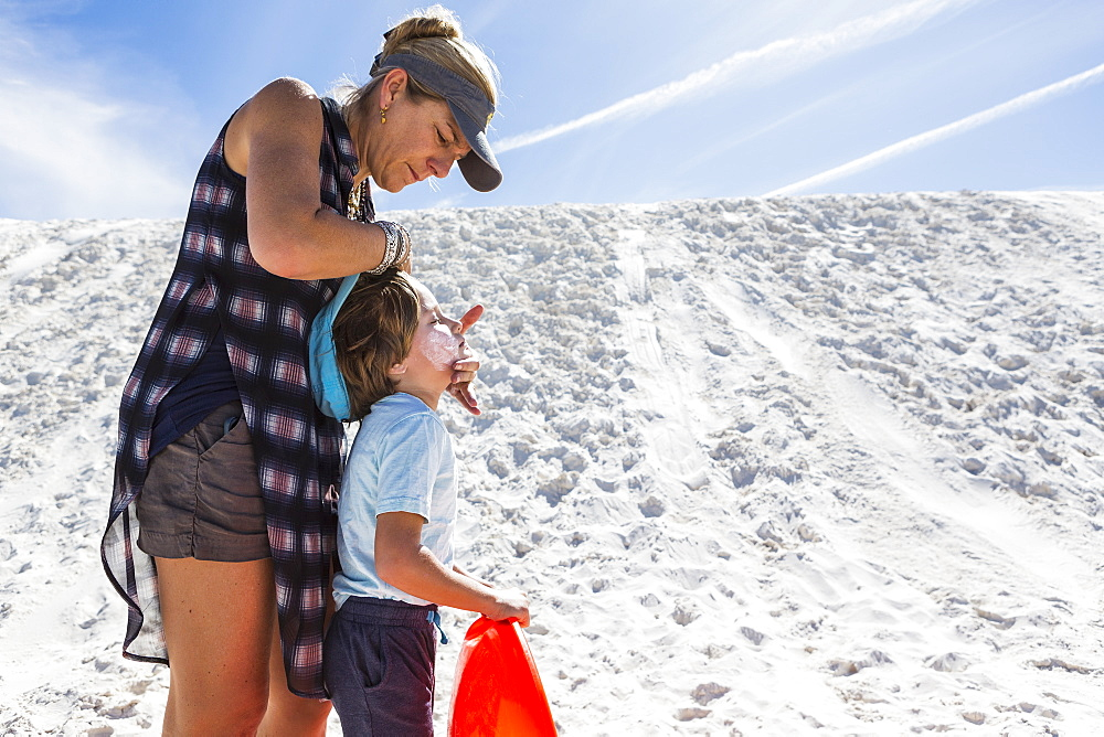 Mother applying sunblock to her child, White Sands National Monument, New Mexico, United States