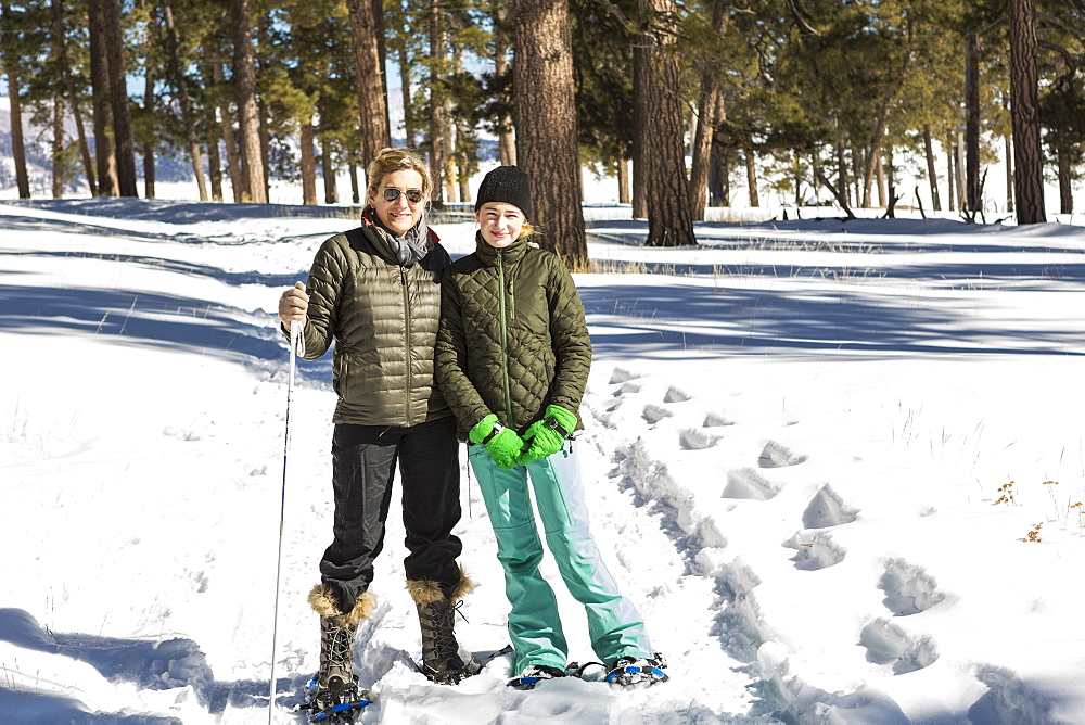 An adult woman and teenage girl in snow shoes in woodland holding ski poles
