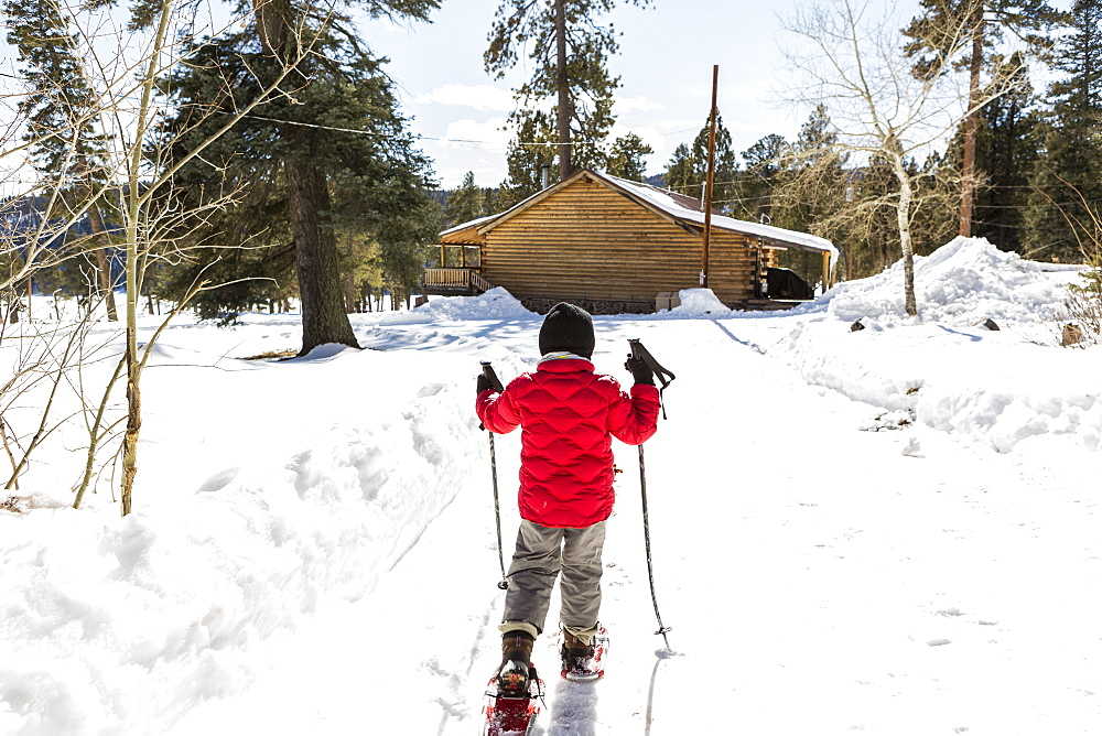 Rear view of young boy in a red jacket snow shoeing