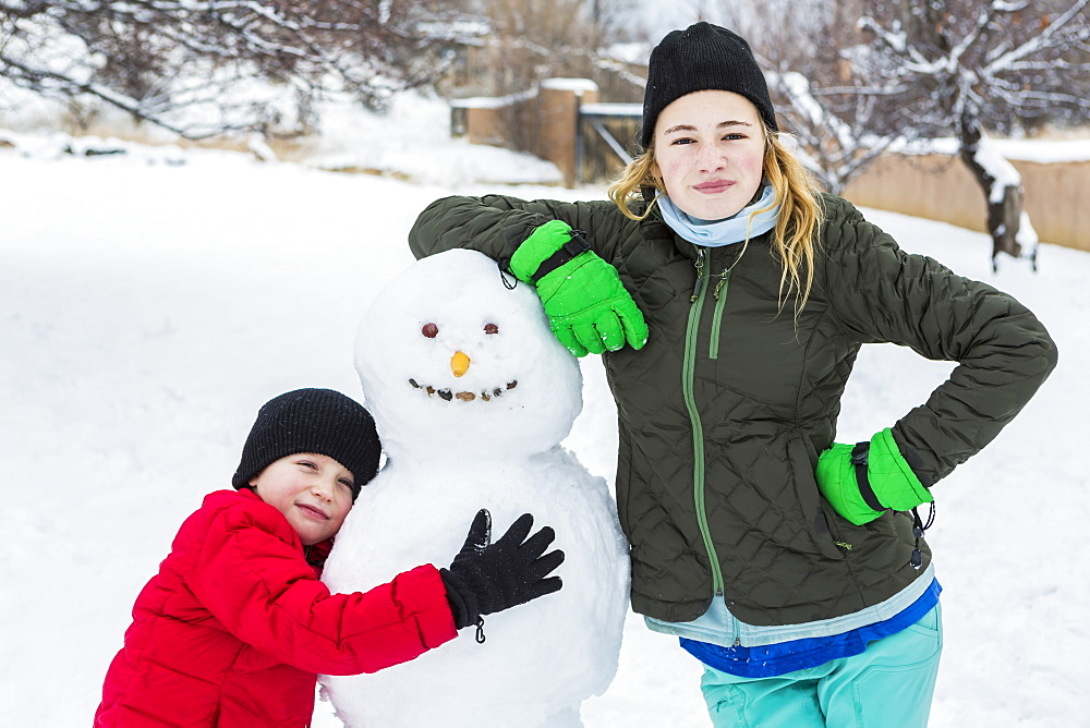Brother and sister, a young boy and teenage girl leaning on snowman in winter