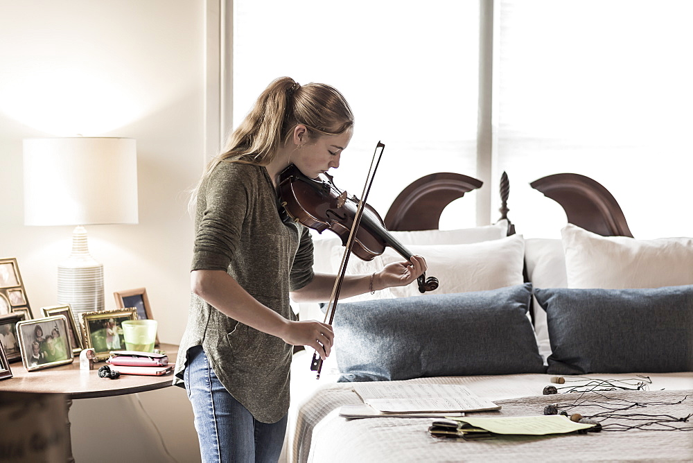 A thirteen year old teenage girl playing violin in bedroom