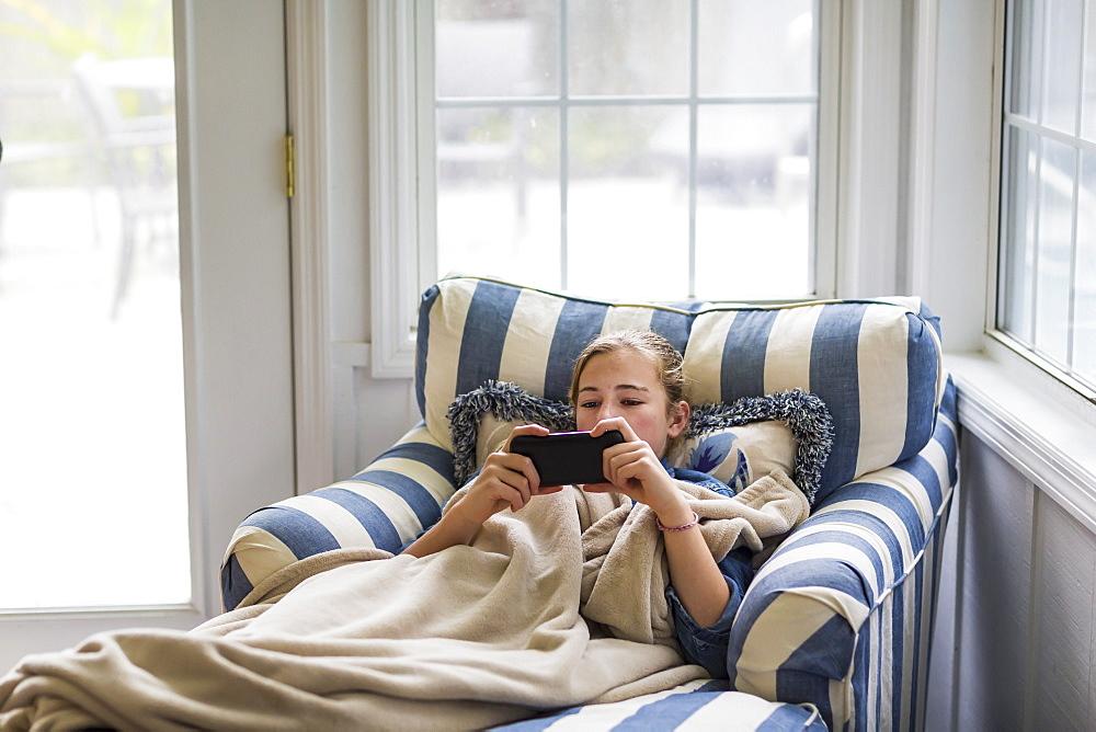 A thirteen year old teenage girl looking at smart phone - 1174-7988
