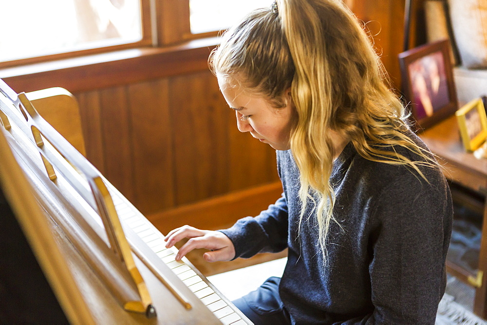 Teenage girl playing piano, practising.