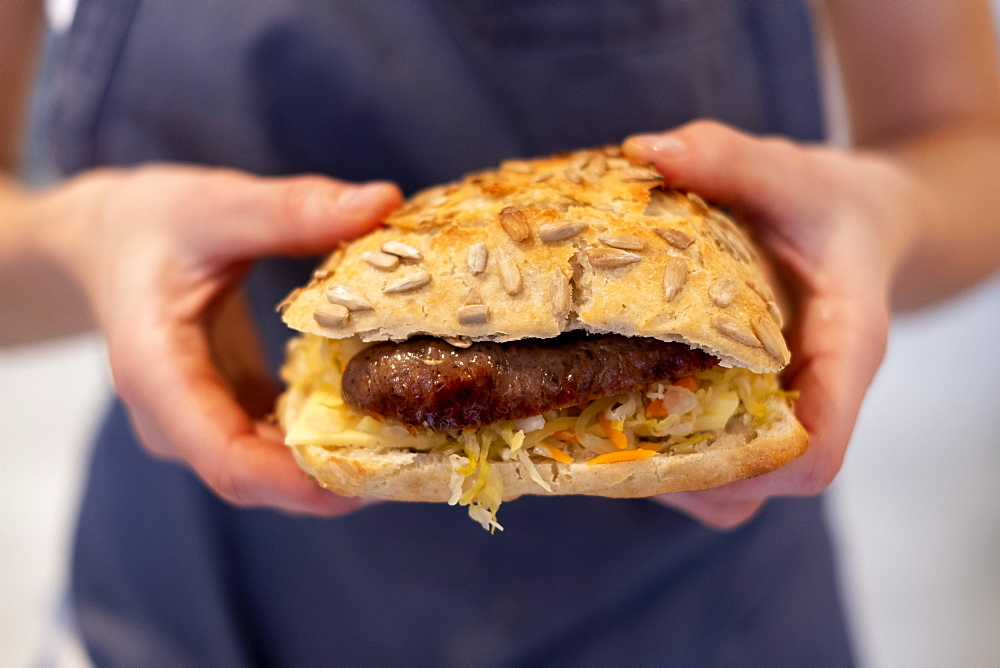 Close up of a person holding freshly made sausage bap, a seeded bun in an artisan bakery.