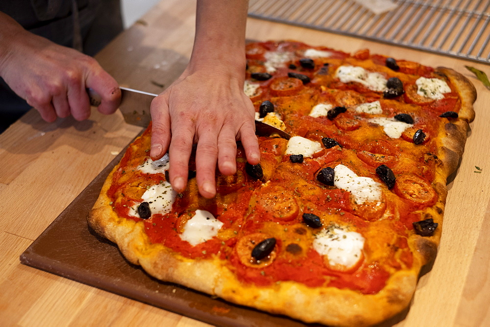High angle close up of person cutting freshly baked pizza in an artisan bakery.