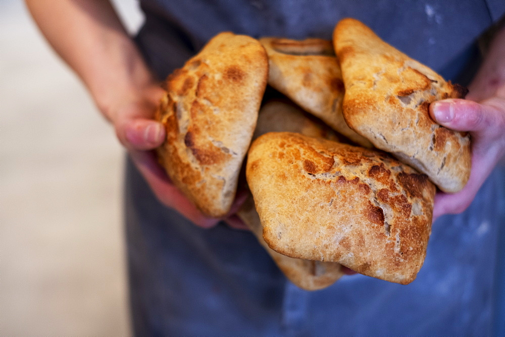 Close up of person holding freshly baked bread rolls in an artisan bakery. - 1174-7995