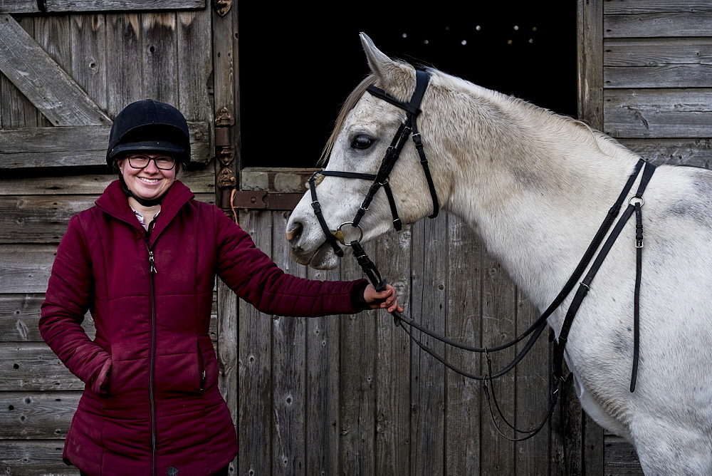 Young woman standing outside stable, holding white Cob horse by it's reins, Berkshire, United Kingdom