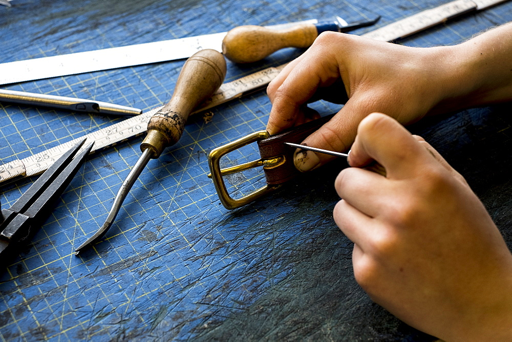 High angle close up of person working in saddler's workshop, attaching buckle to leather strap, Berkshire, United Kingdom