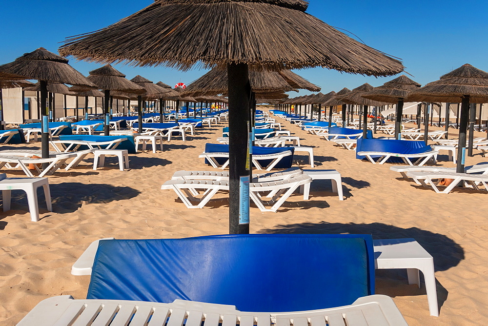 Beach parasols and sunloungers on the beach on Ilha de Tavira, Southern Algarve, Portugal