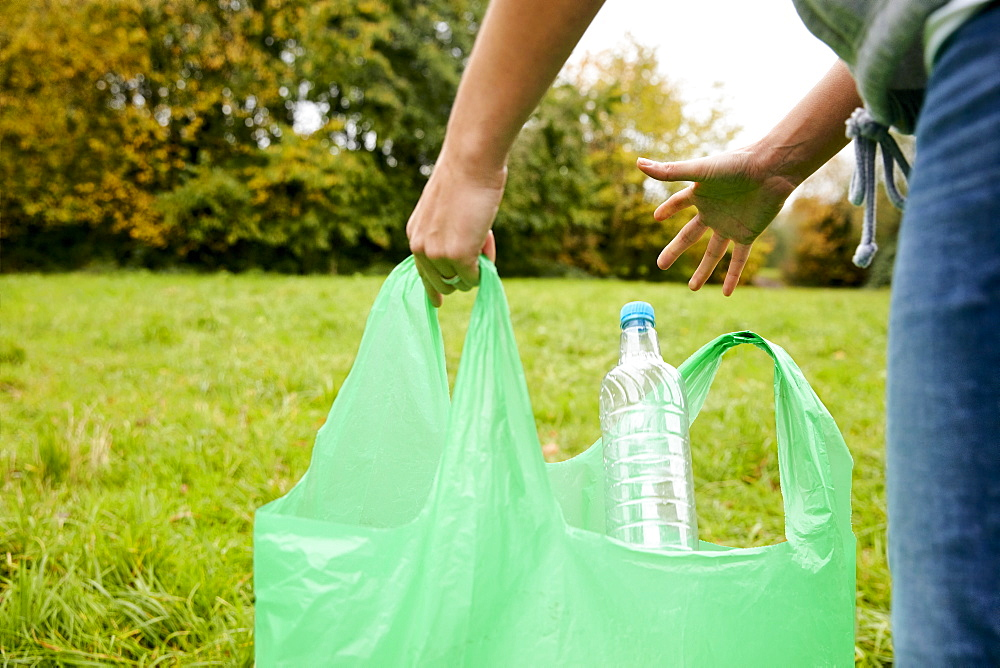 Woman stuffing soft waste plastics into large plastic bottle to make an ecobrick for use as a building block, Bristol, United Kingdom