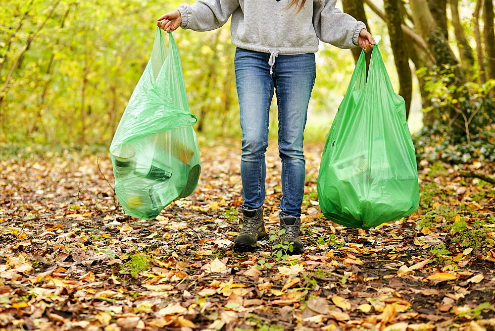 Woman walking in woodland holding two plastic bags full of rubbish, Bristol, United Kingdom