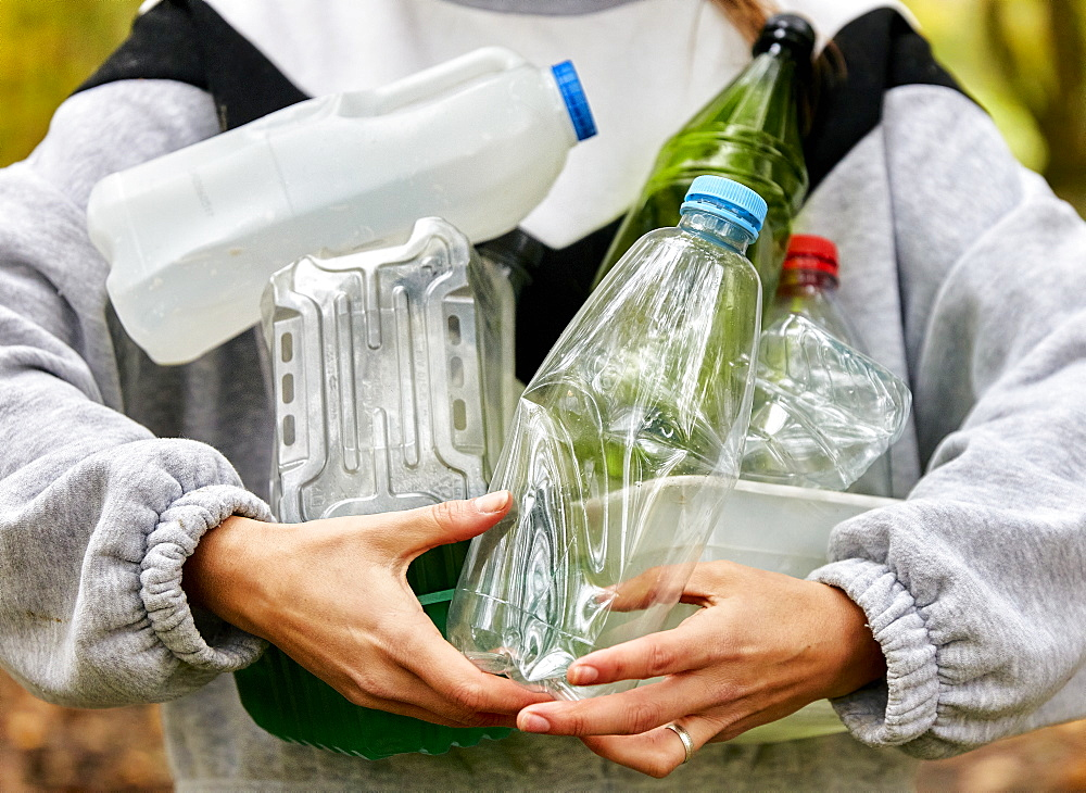 Woman holding armful of used plastic packaging and bottles, Bristol, United Kingdom