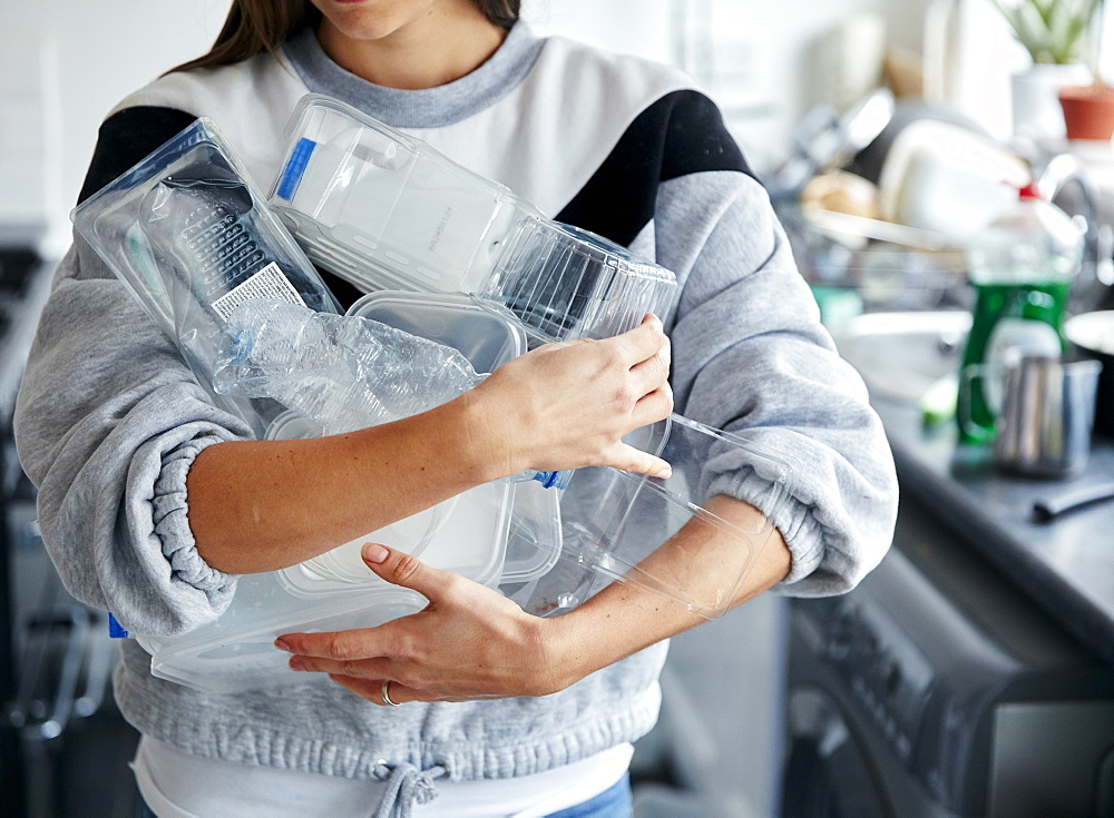 Woman holding armful of used plastic containers in kitchen, Bristol, United Kingdom
