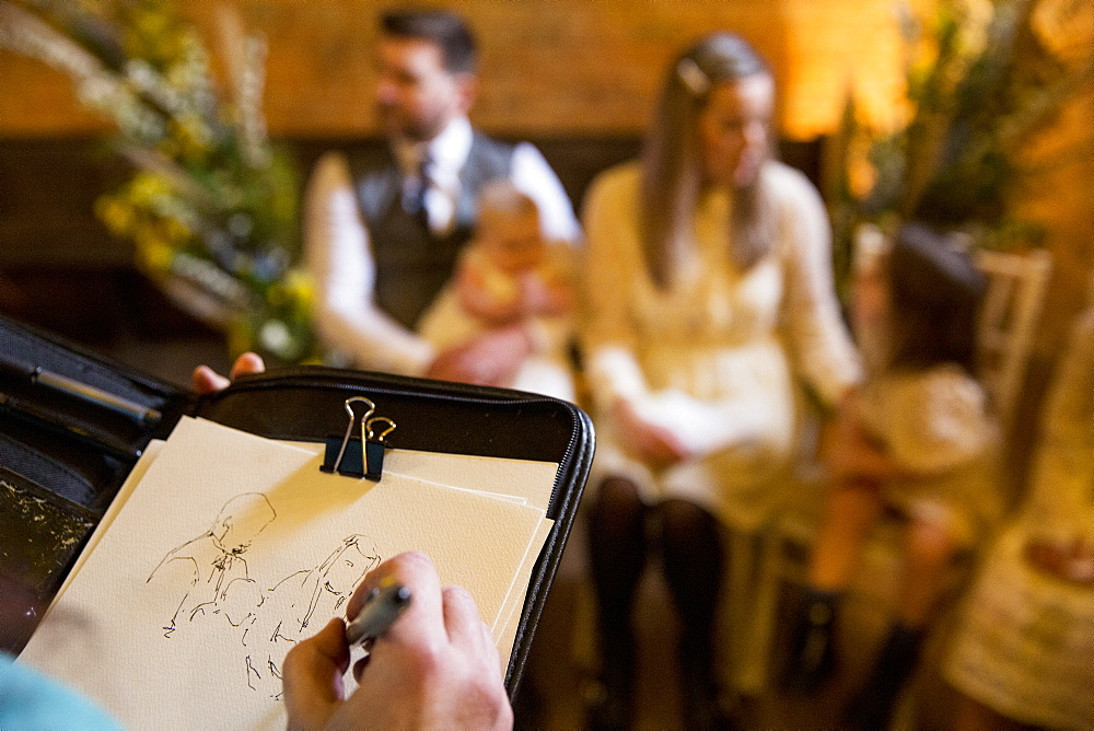 Over the shoulder view of artist sketching family during naming ceremony in an historic barn