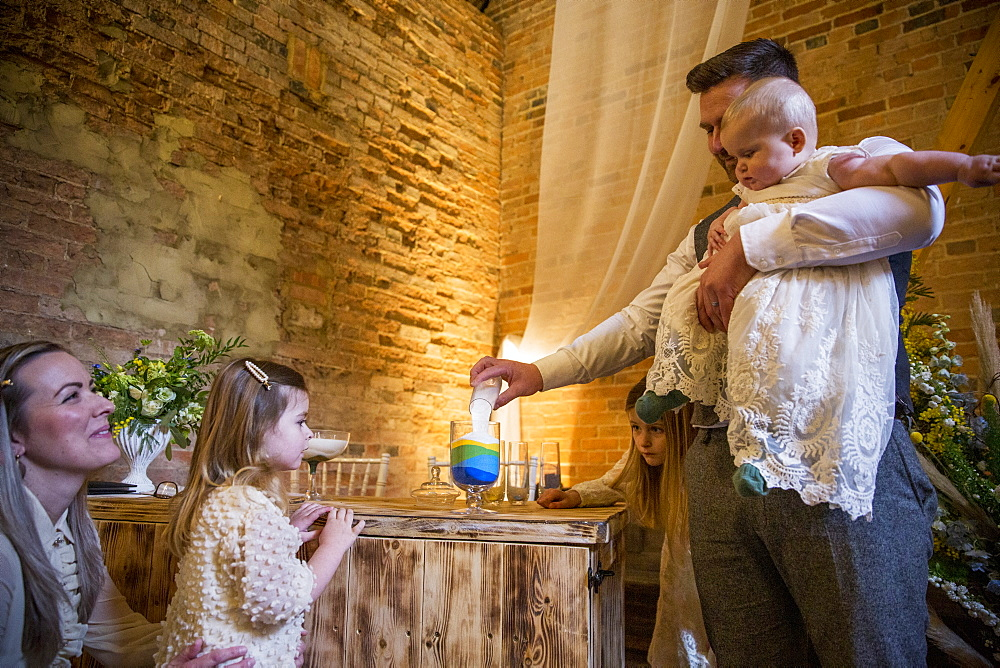 Family pouring coloured sand into glass jar during naming ceremony in an historic barn