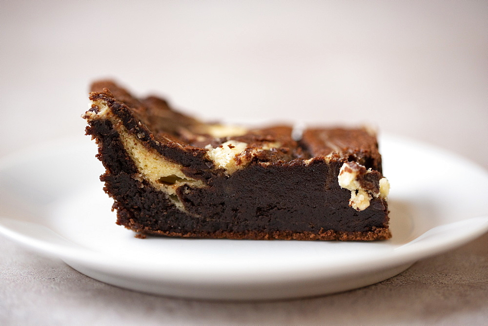 Close up of chocolate cheesecake on white plate in a cafe
