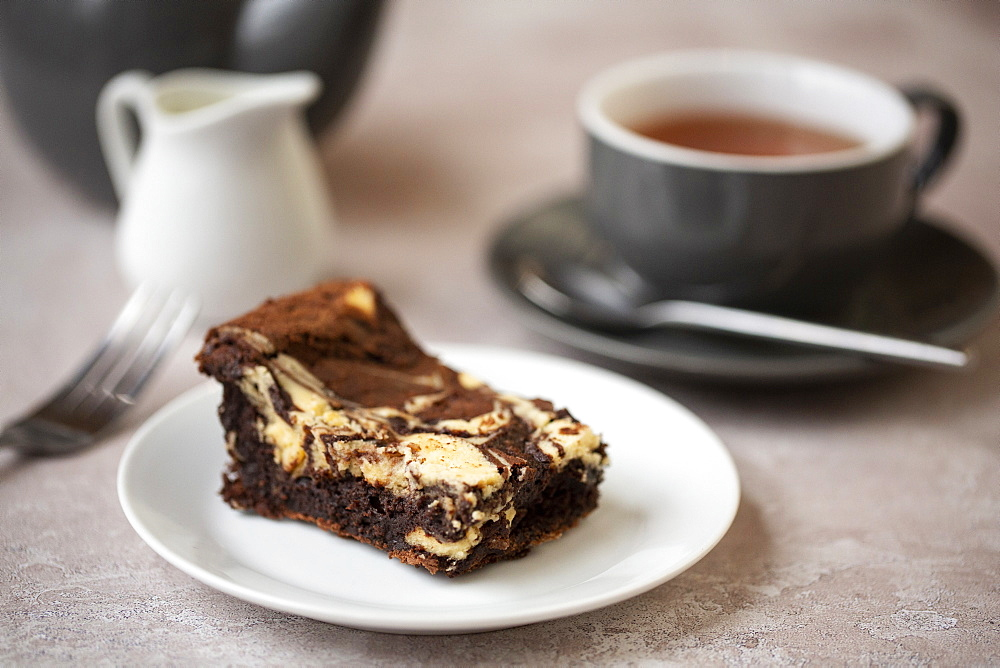 High angle close up of cup of tea and chocolate cheesecake on white plate in a cafe
