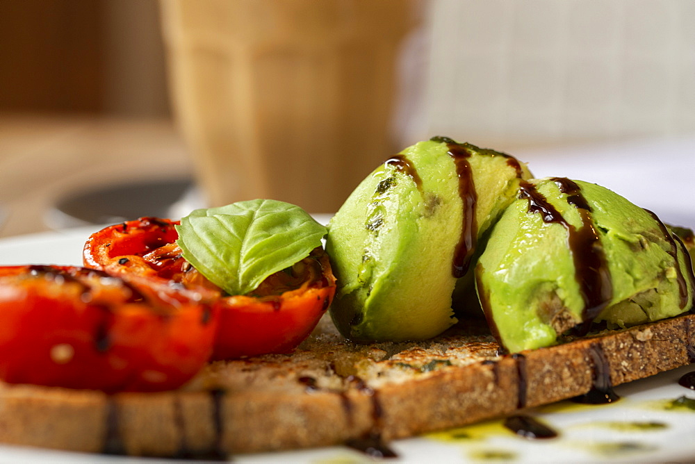 Close up of tomato and avocado bruschetta with balsamic vinegar reduction in a cafe