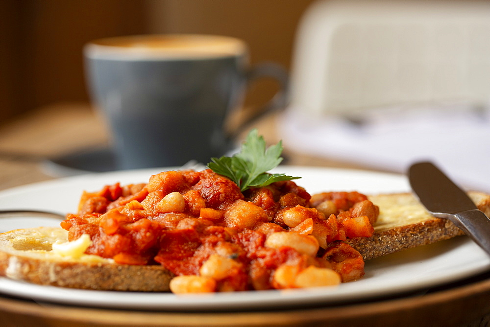 Close up of home made baked beans on sourdough bread in a cafe