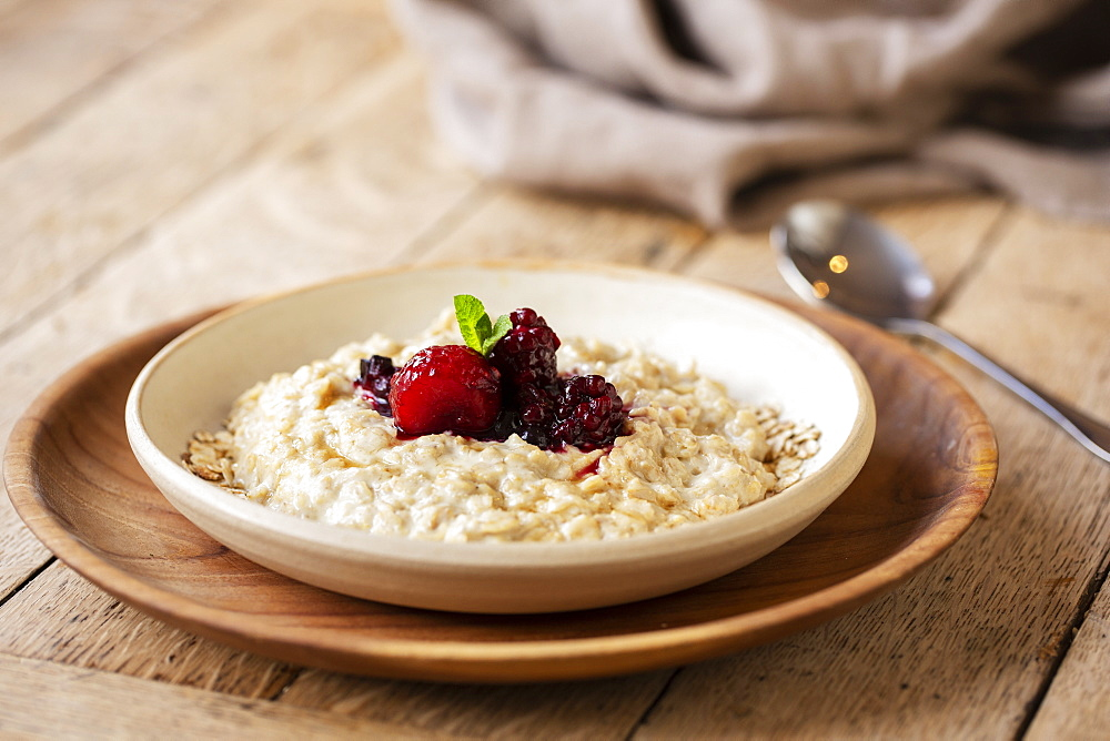 High angle close up of bowl of porridge with mixed berry compote in a cafe