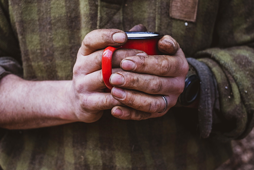 Close up of man with dirty hands holding red enamel mug, Devon, United Kingdom