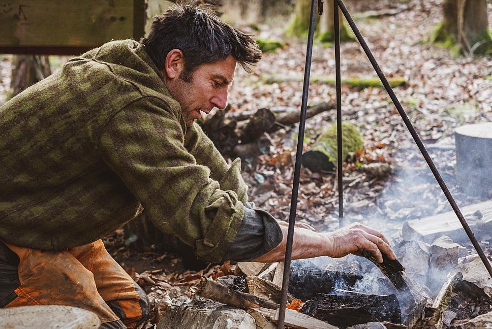 Man sitting by a camp fire in a forest, Devon, United Kingdom