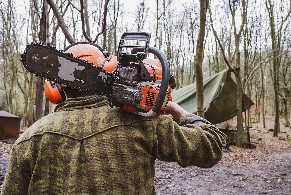 Rear view of man wearing safety gear walking through forest carrying chainsaw on his shoulder, Devon, United Kingdom