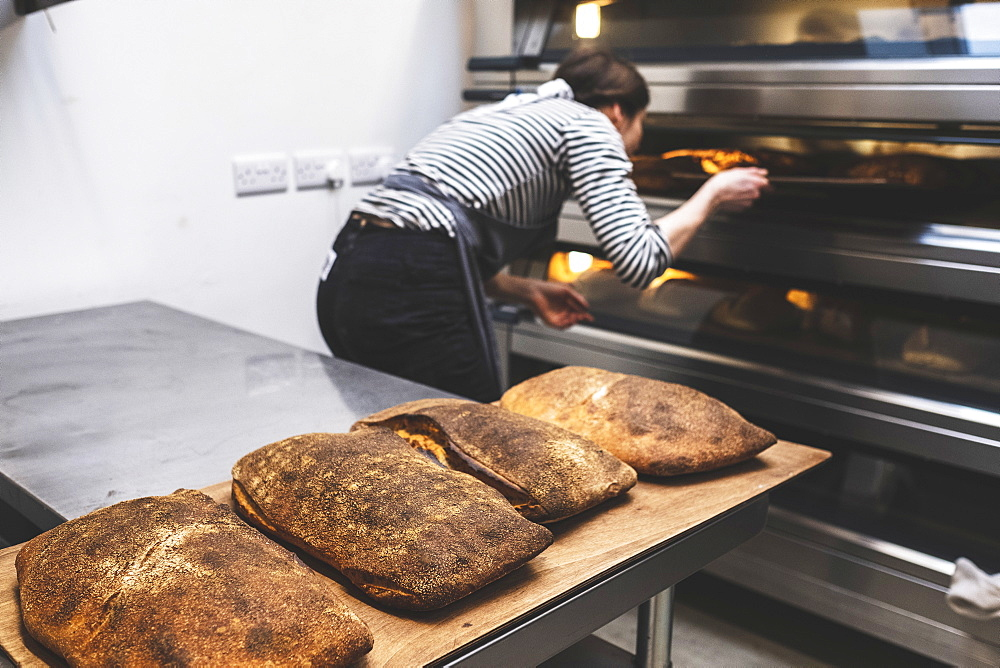 Artisan bakery making special sourdough bread, a baker checking the baked loaves