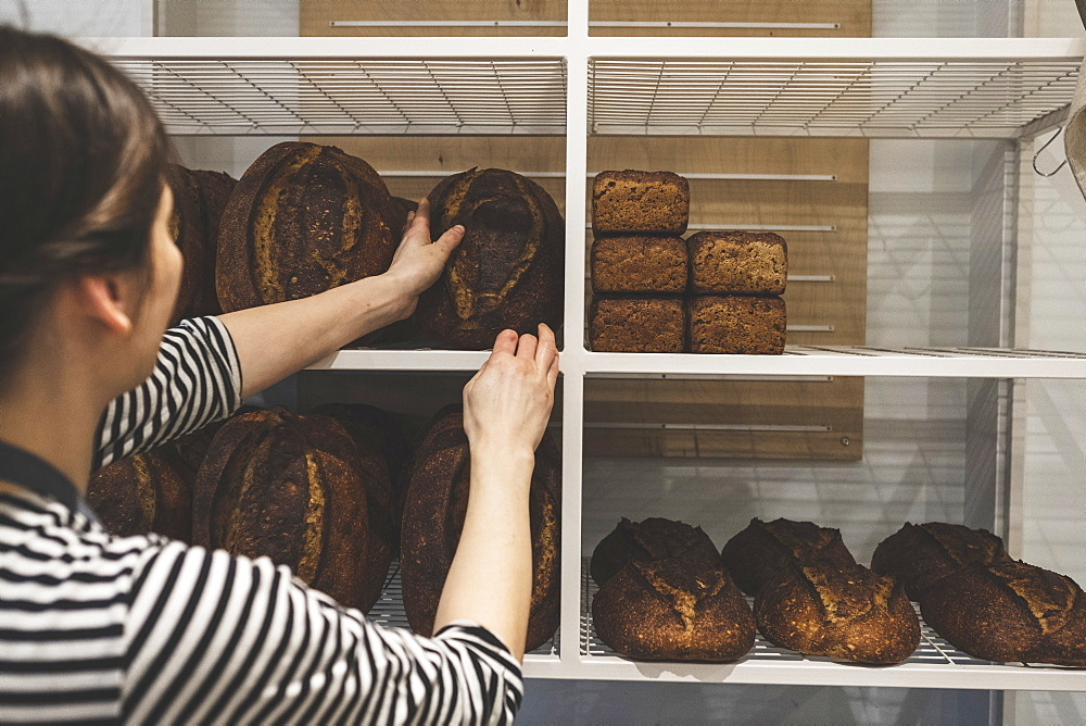 Artisan bakery making special sourdough bread, baker loading shelves with baked goods